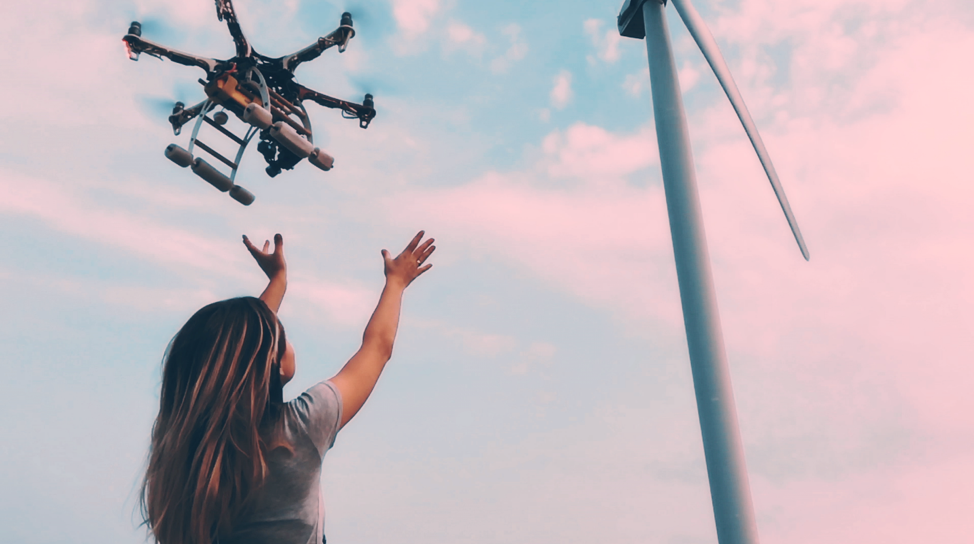 Image of a woman catching a drone coming out of the sky.