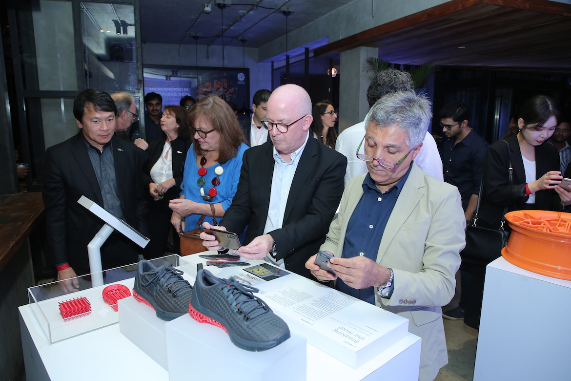 People looking at a display with two 3D-printed Under Armour sneakers.