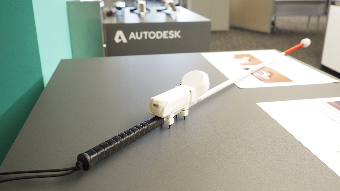 A white cane with a sensor attached to it is displayed on a table.