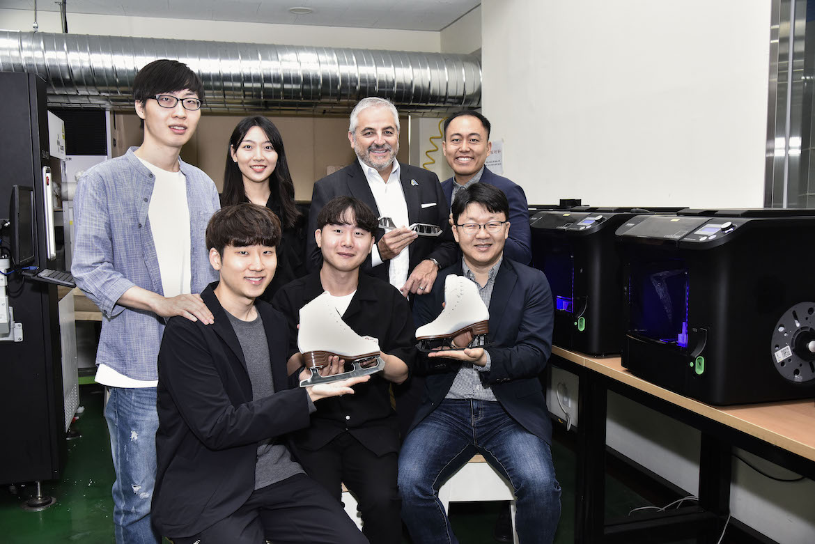 A group of students seated next to a row of 3D printers hold up their new design for a figure skate. The