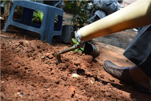A person with a prosthetic arm wearing the avocado connector with a rake attachment