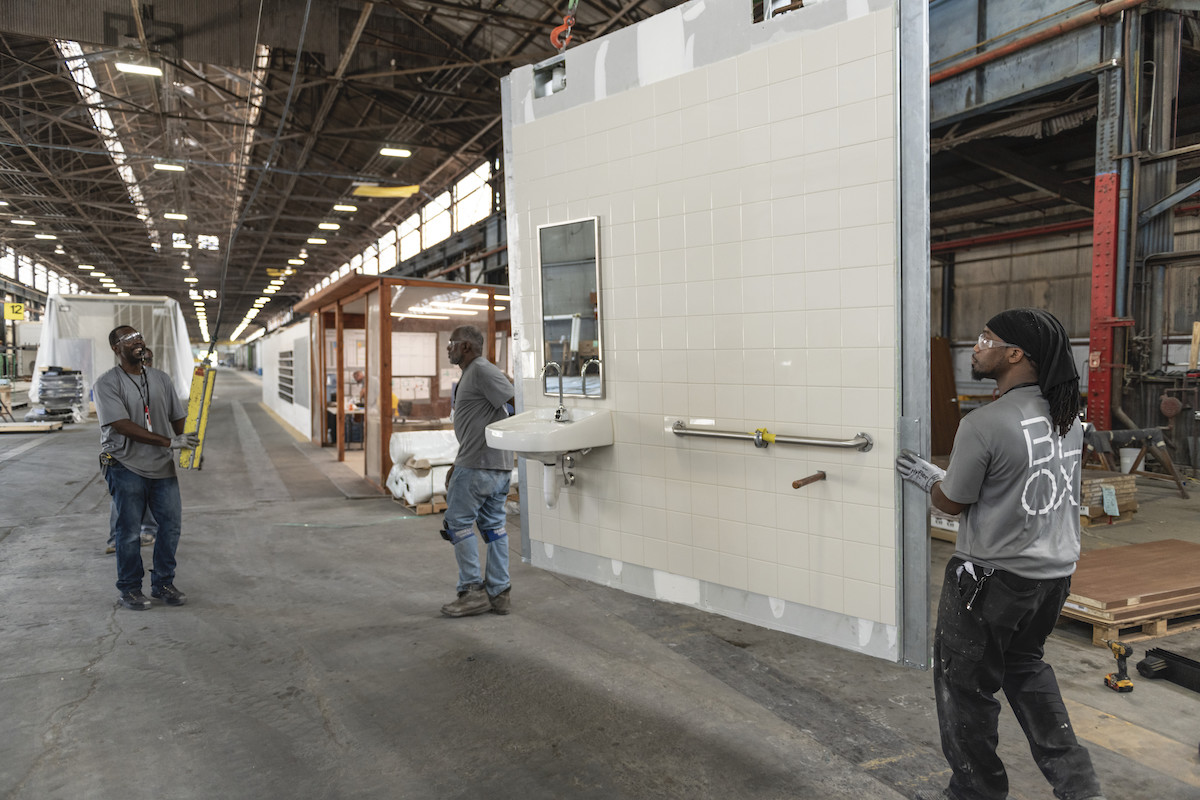 Men transporting a modular wall for a bathroom on a factory floor.