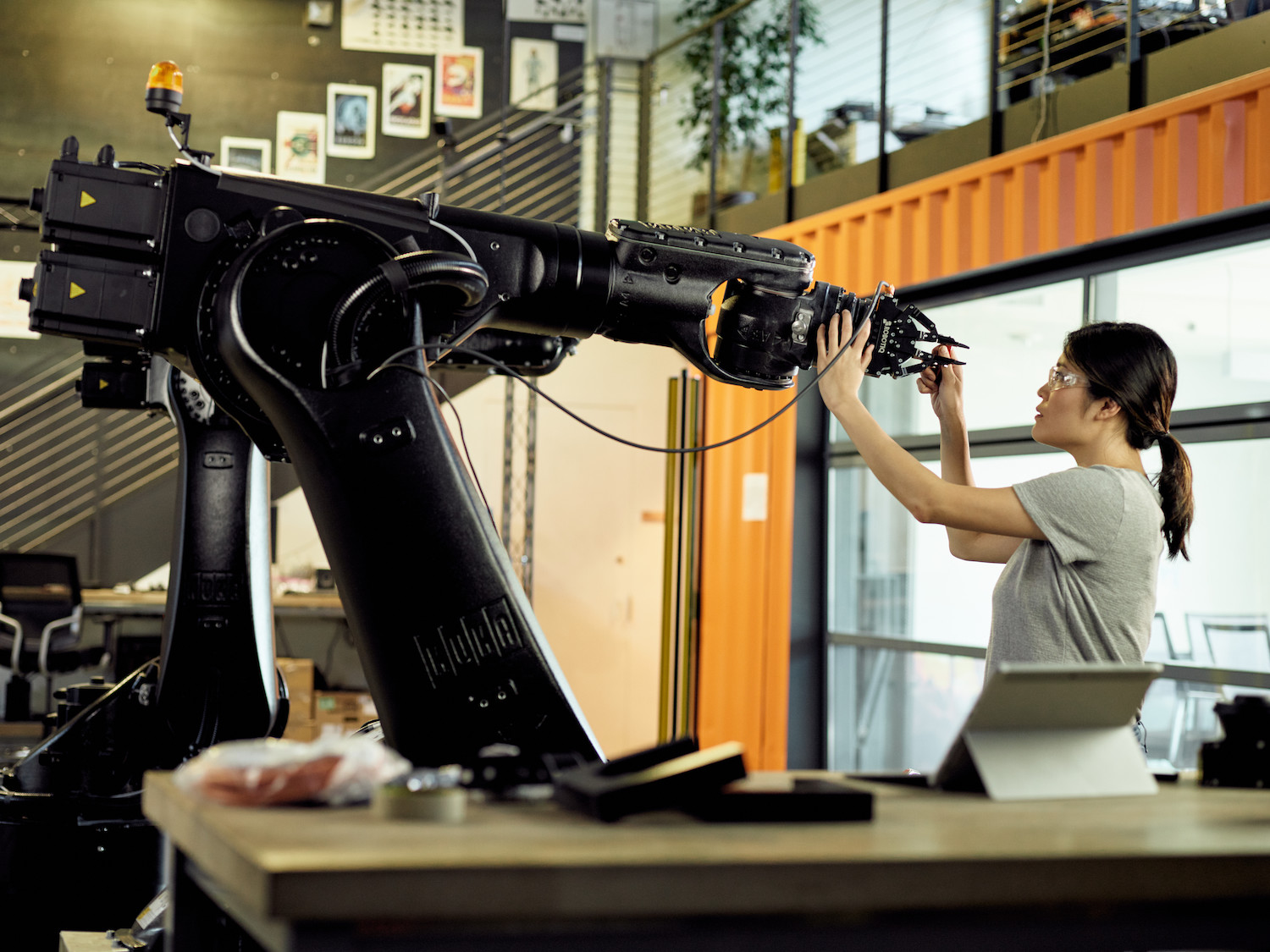 A woman in a lab space touching a large robotic arm.