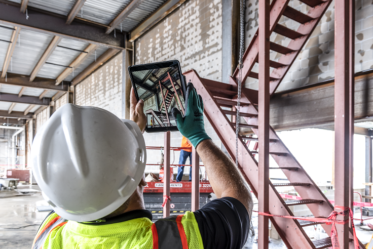 Construction worker looking at a project onsite through an iPad.