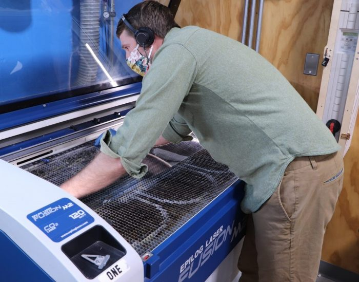 A workshop member at the Bman uses a laser cutter to cut PET material for face shields.