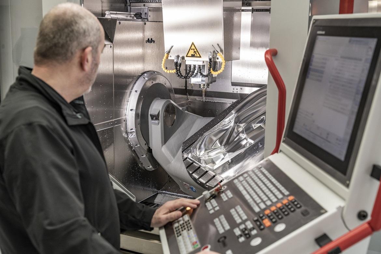 Autodesk PowerMill machining engineer fabricating metal parts using industrial waterjet cutting machine
