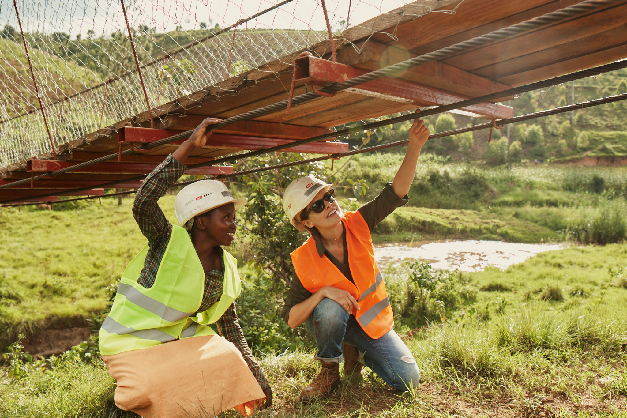 Engineers inspect cables of a B2P foot bridge in Rwanda.