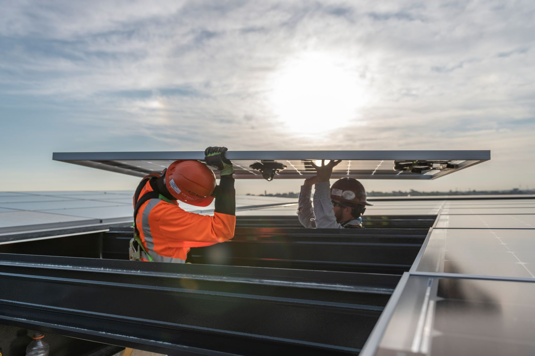 Workers installing solar panels on a building in San Antonio, TX.